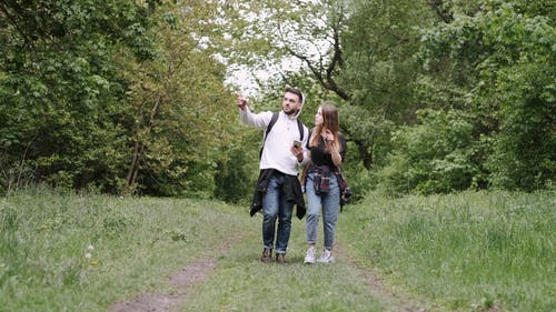 Man and Woman Walking on Unpaved Pathway