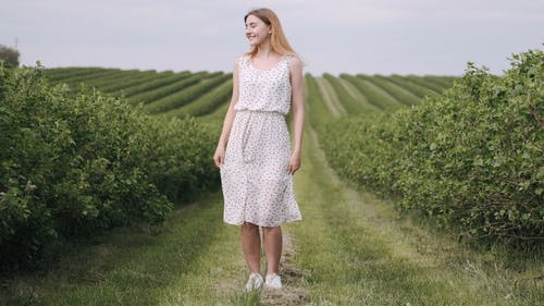 A Woman In White Printed Dress Standing In The Field