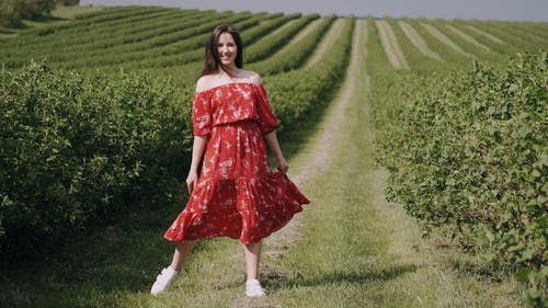 A Woman In Red Floral Dress Posing In A Plantation Field