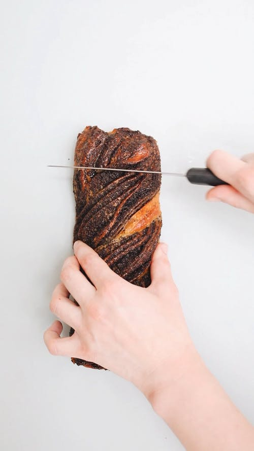 Person Slicing a Bread Using a Knife