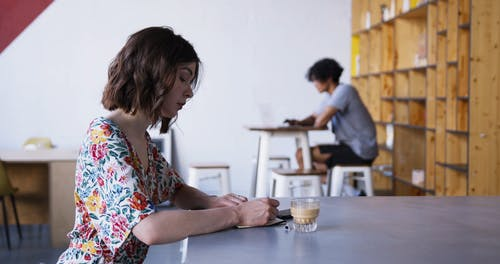 A Woman Writing Notes While Having A Coffee