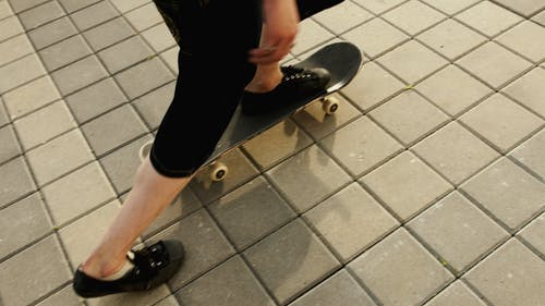 Person in Black Shorts Riding a Skateboard