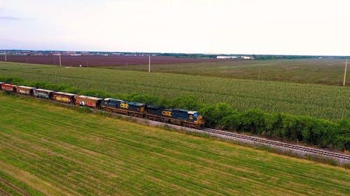 A Train Traveling On A Railroad Crossing A Farm Field