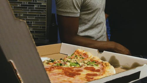 A Man Grabbing A Slice of Pizza