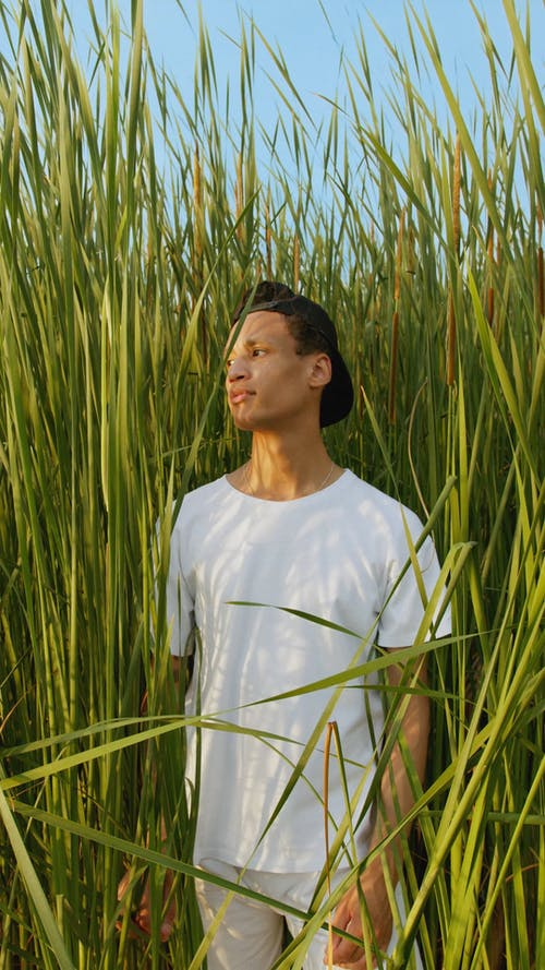 A Young Man Standing Along The Tall Grasses