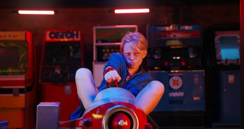 A Young Teen Riding A Kids Toy In An Amusement Center