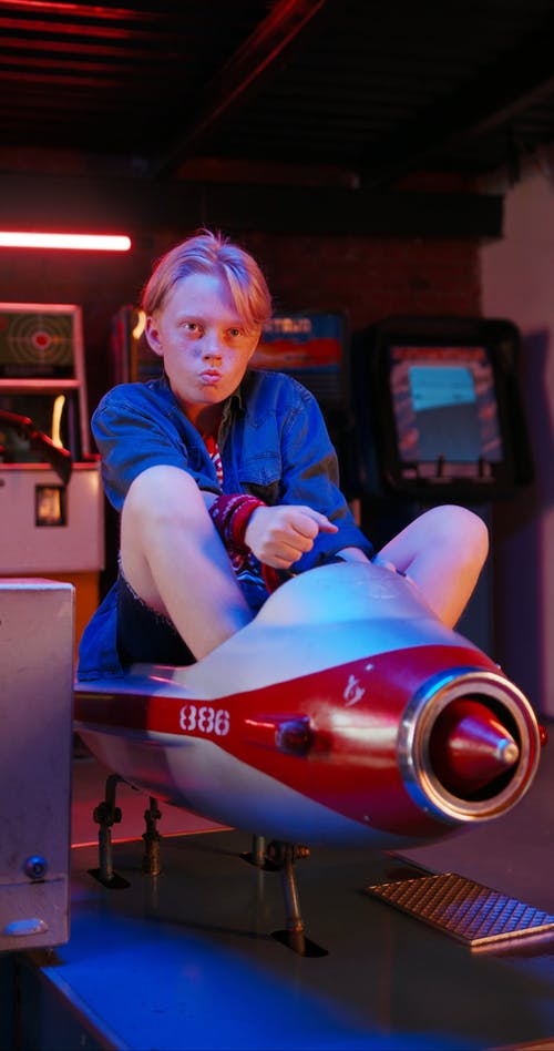 A Young Teen Riding A Toy Plane In An arcade