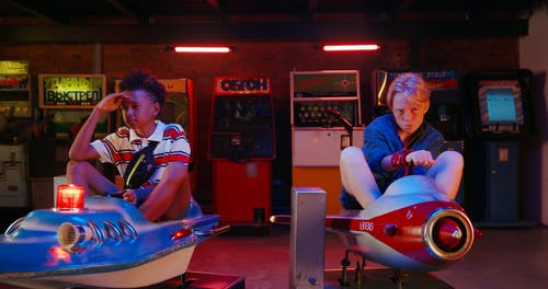 Two Young Teens Riding On Kid Toys