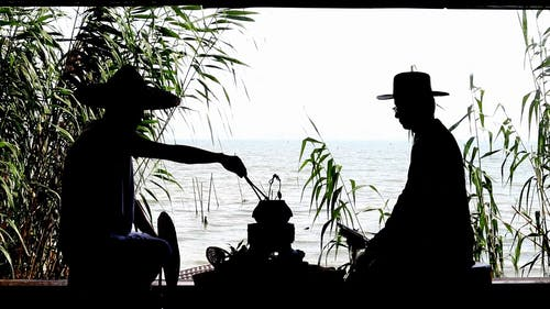 Silhouette of People Sitting by the Lake