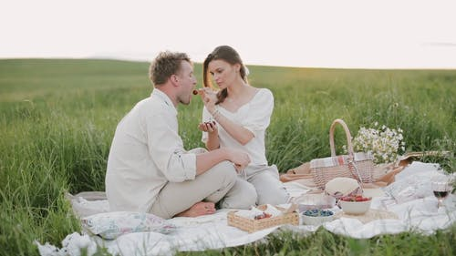 Couple Having a Picnic on Grass Field