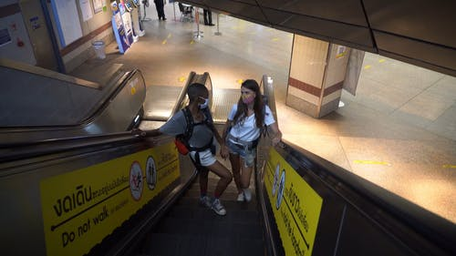 Two Persons Riding the Escalators While Looking at Each Other