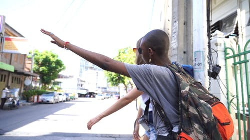 Two Female Backpackers Hitch Hiking A Ride