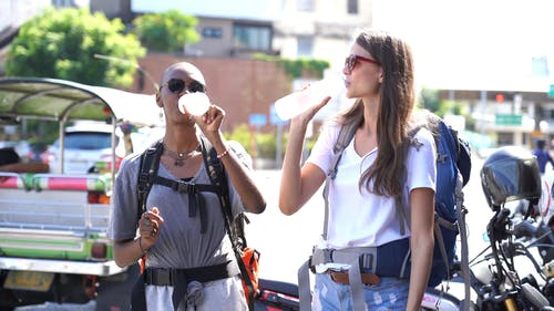 Two Tourists Drinking Bottled Water In The Street
