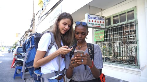 Two Women Tourist Using Their Smartphone To Find Directions