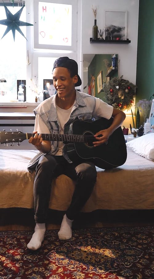 A Young Man Playing A Guitar Inside His Room