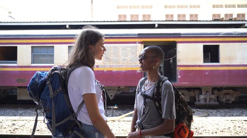 Two Women Talking to Each Other While Standing on Railway Platform