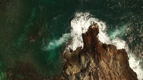 Top View of Sea Waves Crashing on Rock Formations