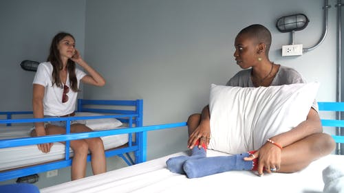 Two Woman Talking to Each Other While Sitting on Their Bed