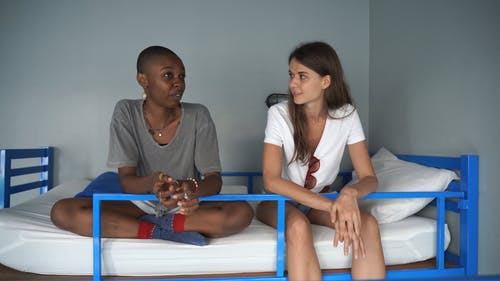 Two Women Talking to Each Other While Sitting on Bed