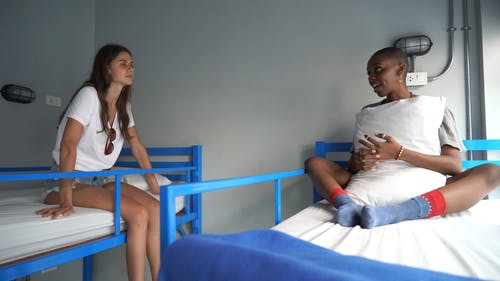 Two Women Talking to Each Other While Sitting on Their Bed