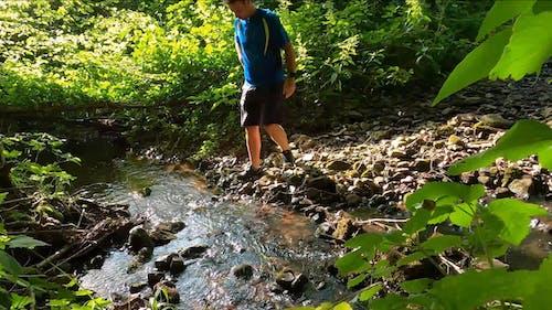 A Man Crossing A Stream Stepping On Rocks