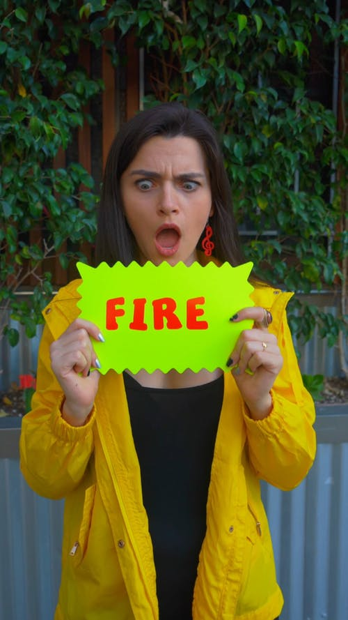 A Woman Holding A Sign Indicating Fire