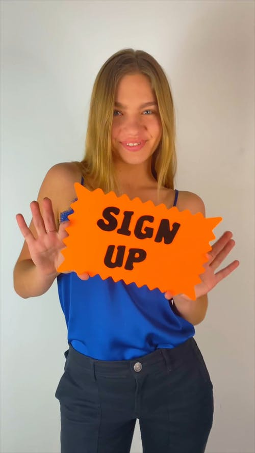 A Woman Holding A Sign Encouraging To Sign Up