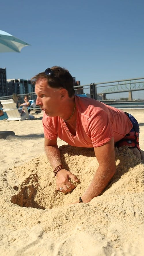 A Man Digging Money From The Sand