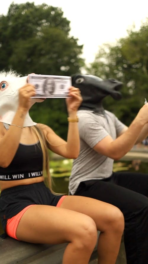 People With Pony Mask Eating Phony Paper Money