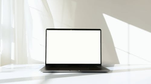 Laptop Computer on White Surface Against White Background