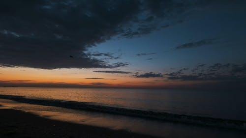 Sea Waves Crashing on Beach Shore During Sunset