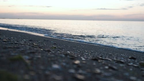 Low Angle Shot of Sea Waves Crashing on Beach Shore