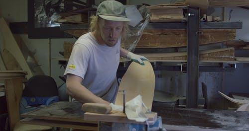 Man Making a Skateboard in His Workshop