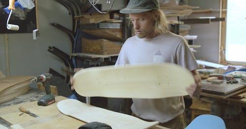 Man Brushing His Skateboard