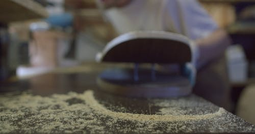 Man Blowing Off the Sawdust from His Work Table