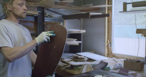 A Craftsman Shaping The Edges Of A Skateboard