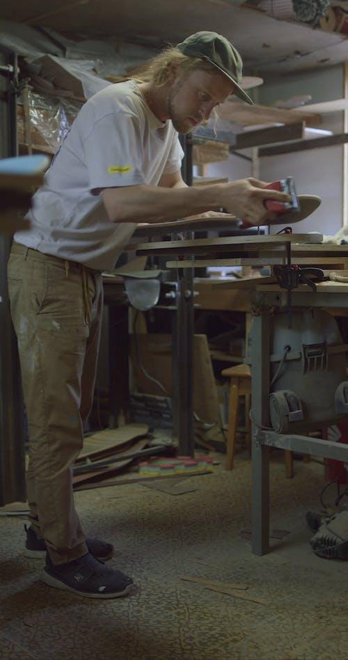 A Man Manually Sanding The Edges Of A Skateboard