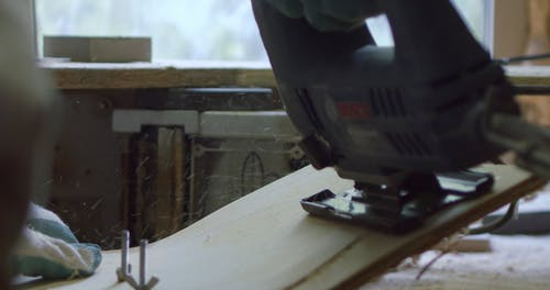 A Man Cutting A Wooden Board With An Electric Saw