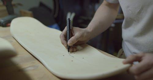 A Man Marking An Unfinished Skateboard