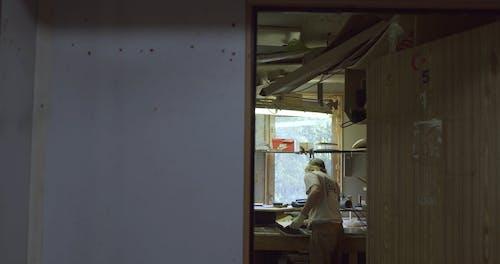 A Craftsman Making a Skateboard in His Workshop