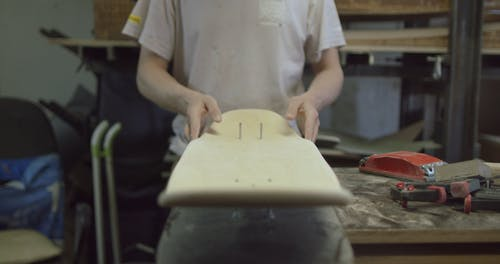 A Craftsman Shaping a Skateboard in Progress then Blowing Off the Wood Dust