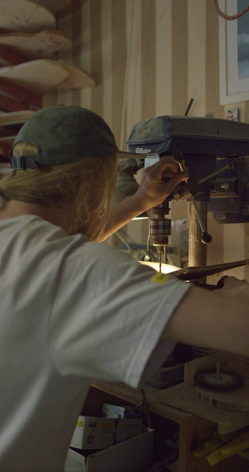 A Craftsman Using a Drilling Machine in Making a Skateboard