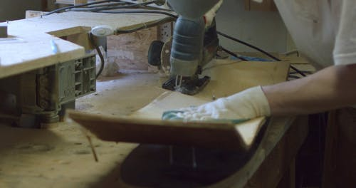 A Craftsman Using a Circular Saw in Making a Skateboard