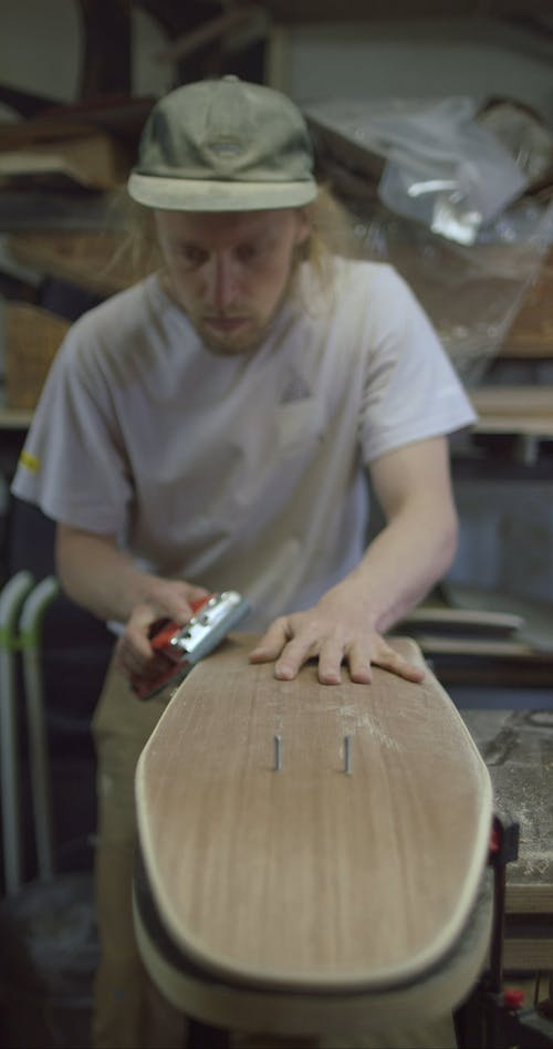 A Craftsman Smoothing a Skateboard in Process