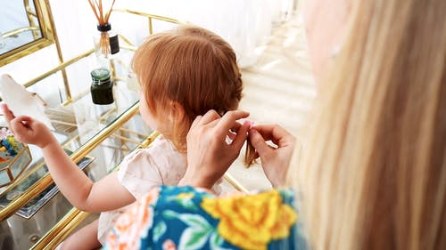 Mom Tying Her Daughter's Hair With Pink Ribbon