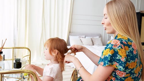 Mom Fixing Her Daughter's Hair While Smiling