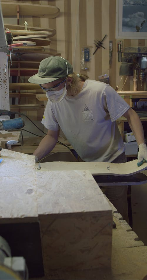 A man Shaping a Wood Board Into a Skateboard