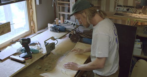 A Man Shaping A Wood Into A Skateboard Using A Pattern