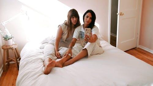A Couple Taking Selfie In Bed