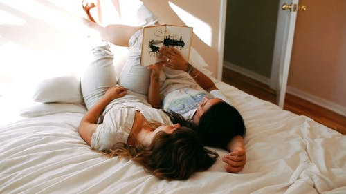 A Couple Reading A Book Together In Bed